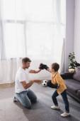 roztomilý chlapec v boxerských rukavicích bojuje s otcem stojící na kolenou na podlaze