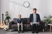 komoly üzletember és a fia a formális viselet ül laptopok kanapén otthon, és a kamerába