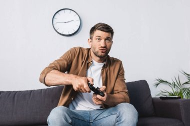 KYIV, UKRAINE - JUNE 9, 2020: excited man playing video game with joystick while sitting on sofa stock vector
