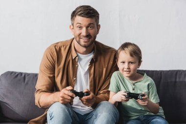 KYIV, UKRAINE - JUNE 9, 2020: excited father and son sitting on sofa and playing video game with joysticks stock vector
