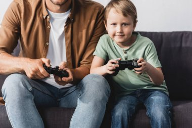 KYIV, UKRAINE - JUNE 9, 2020: cropped view of man with attentive son playing video game with joysticks stock vector