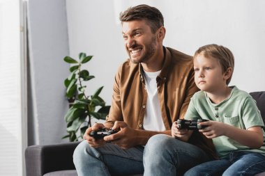 KYIV, UKRAINE - JUNE 9, 2020: excited father and concentrated son playing video game with joysticks stock vector
