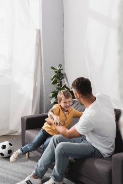 Father and happy son jokingly fighting on sofa near soccer ball stock vector