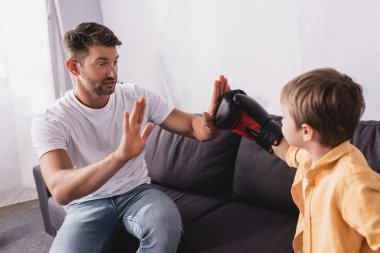 Handsome man sitting on sofa and fighting with son wearing boxing gloves stock vector