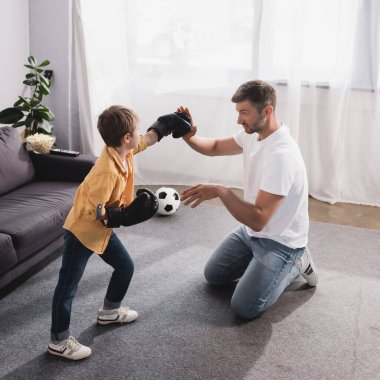 Handsome man fighting with cute son in boxing gloves on floor stock vector