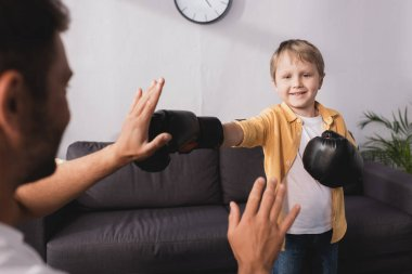 Selective focus of smiling boy in boxing gloves fighting with father stock vector