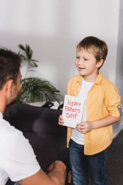 Smiling boy presenting happy fathers day greeting card to father stock vector