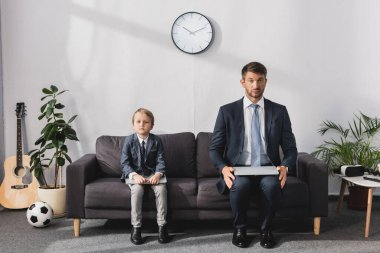 Serious businessman and his son in formal wear sitting with laptops on sofa at home and looking at camera stock vector