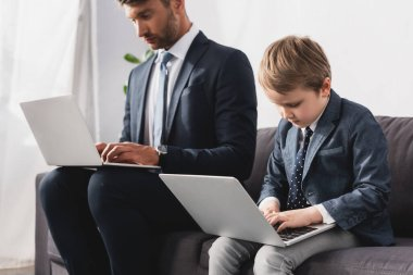 Handsome businessman and his son in formal wear using laptops at home stock vector
