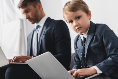 Adorable, serious boy and his father in formal wear using laptops at home stock vector