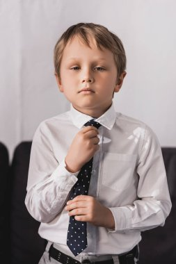 serious, cute boy in white shirt putting tie on and looking at camera