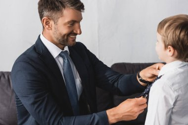 happy businessman putting tie on adorable son at home