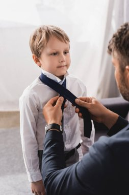 selective focus of businessman putting tie on cute, serious son at home