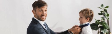 panoramic crop of businessman smiling at camera while putting tie on adorable son at home