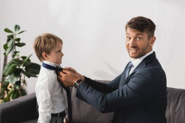 smiling businessman in formal wear looking at camera while putting tie on adorable son at home