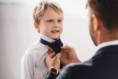 selective focus of businessman putting tie on happy, cute son at home