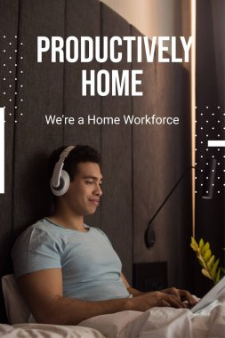 bi-racial man listening music in headphones and using laptop near productively home, were a home workforce lettering