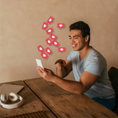happy mixed race man pointing with finger at smartphone, laptop, headphones and virtual hearts illustration