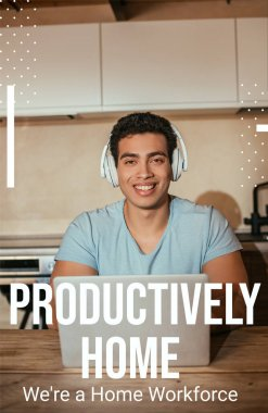 smiling bi-racial man listening music in headphones and using laptop near productively home, were a home workforce lettering