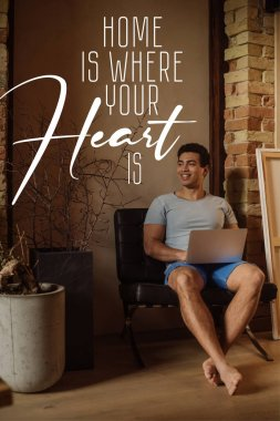Happy mixed race freelancer chilling with laptop near lettering home is where your heart is lettering stock vector