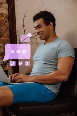 Smiling mixed race freelancer using laptop near virtual speech bubble with chat stock vector
