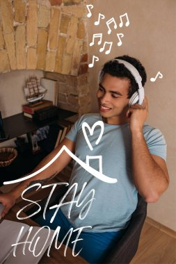 smiling mixed race man touching headphones near stay home lettering
