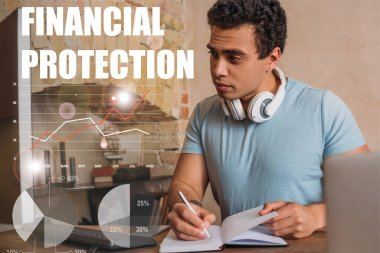 Selective focus of handsome mixed race freelancer writing in notebook near computer monitor and financial protection lettering stock vector