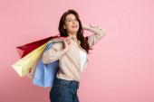 Krásná brunetka žena usmívá na kameru, zatímco drží barevné nákupní tašky na růžovém pozadí