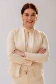 Pozitivní brunetka žena ve formálním oblečení se zkříženými pažemi s úsměvem na kameru izolované na šedé