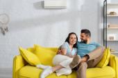Hezký vousatý muž objímající usmívající se přítelkyně na gauči v obývacím pokoji