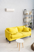 Photo Interior of living room with yellow couch and air conditioner on wall