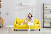 Krásná žena se usmívá na kameru, zatímco sedí na pohovce v obývacím pokoji