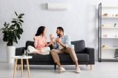 Positives Paar lächelt sich an, während es zu Hause auf dem Sofa unter der Klimaanlage sitzt