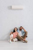 Junges Paar lächelt in die Kamera, während es zu Hause unter einer Klimaanlage auf dem Boden sitzt
