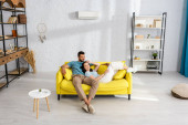 Usmívající se dívka dívá na kameru, zatímco leží na pohovce v blízkosti přítele v obývacím pokoji