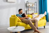 Selektiver Fokus der Fernbedienung von Klimaanlage und Anlage auf Couchtisch und junges Paar auf Couch zu Hause