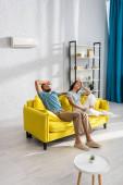 Mann leidet unter Hitze nahe müder Freundin auf Sofa zu Hause