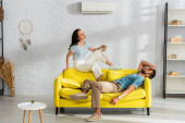 Nő gazdaság könyv szenvedés közben hő közelében barátja kanapén a nappaliban