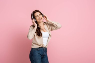 Positive woman listening music in headphones on pink background