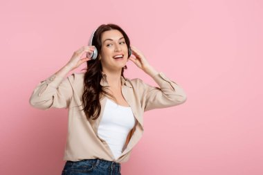 Cheerful woman in headphones looking away on pink background