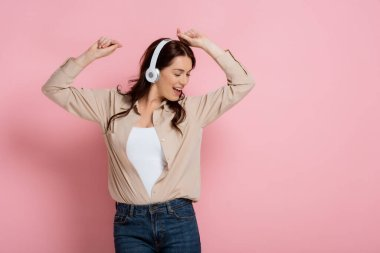 Beautiful woman in headphones dancing and singing on pink background