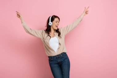 Cheerful woman pointing with fingers while listening music in headphones on pink background