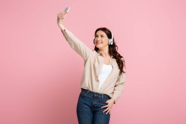 Smiling woman in headphones taking selfie with smartphone on pink background, concept of body positive