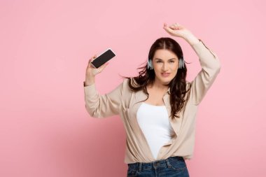 Positive woman in headphones holding smartphone and looking at camera on pink background