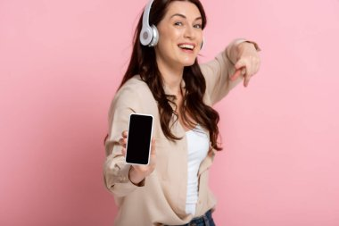 Selective focus of cheerful woman in headphones pointing with finger at smartphone on pink background