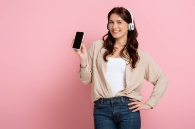 Beautiful woman in headphones holding smartphone and smiling at camera on pink background