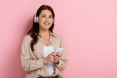 Attractive woman smiling at camera while using headphones and smartphone on pink background