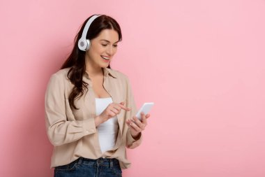 Positive woman in headphones pointing with finger at smartphone on pink background