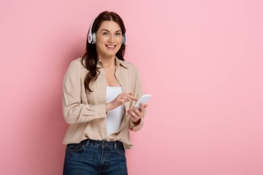 Attractive woman smiling at camera while listening music in headphones and using smartphone on pink background