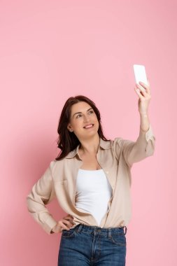 Attractive woman smiling while taking selfie with smartphone on pink background